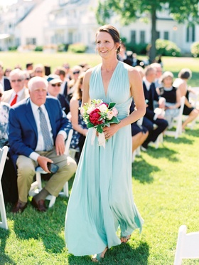 Bridesmaid walking down grass aisle in mint green blue v neck bridesmaid dress pink peony bouquet