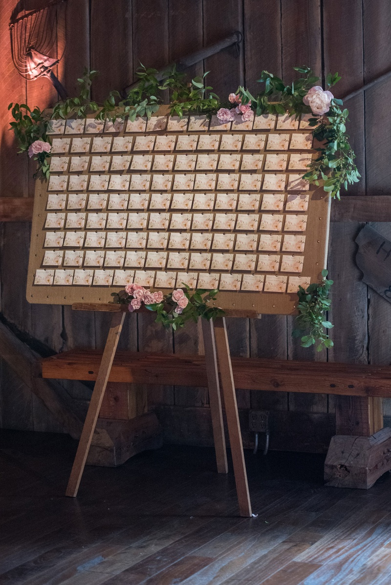 escort card display on easel with greenery, escort card with pink floral details