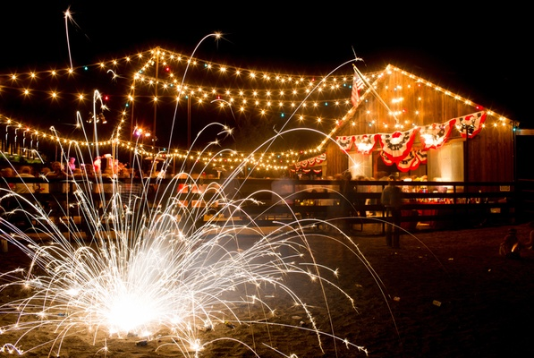 Sparkler on ground in front of fourth of july party at barn