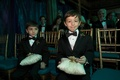 two ring bearers wearing tuxedos hold pillows