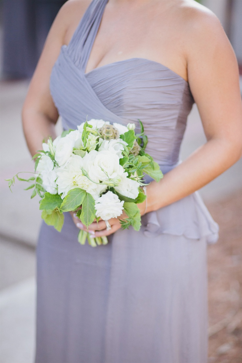 Bridesmaid in purple dress holding white and green bouquet