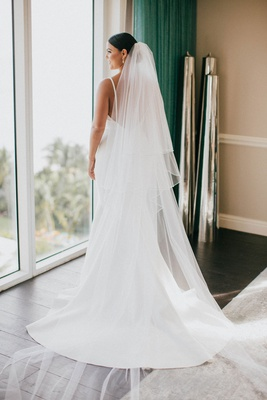 bride in elegant crepe wedding dress with low back spaghetti straps updo bun veil cathedral