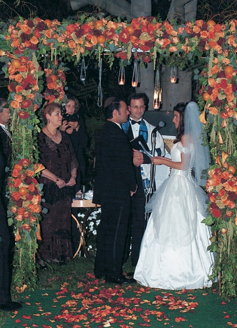 ceremony under chuppah decorated with orange flowers and greenery