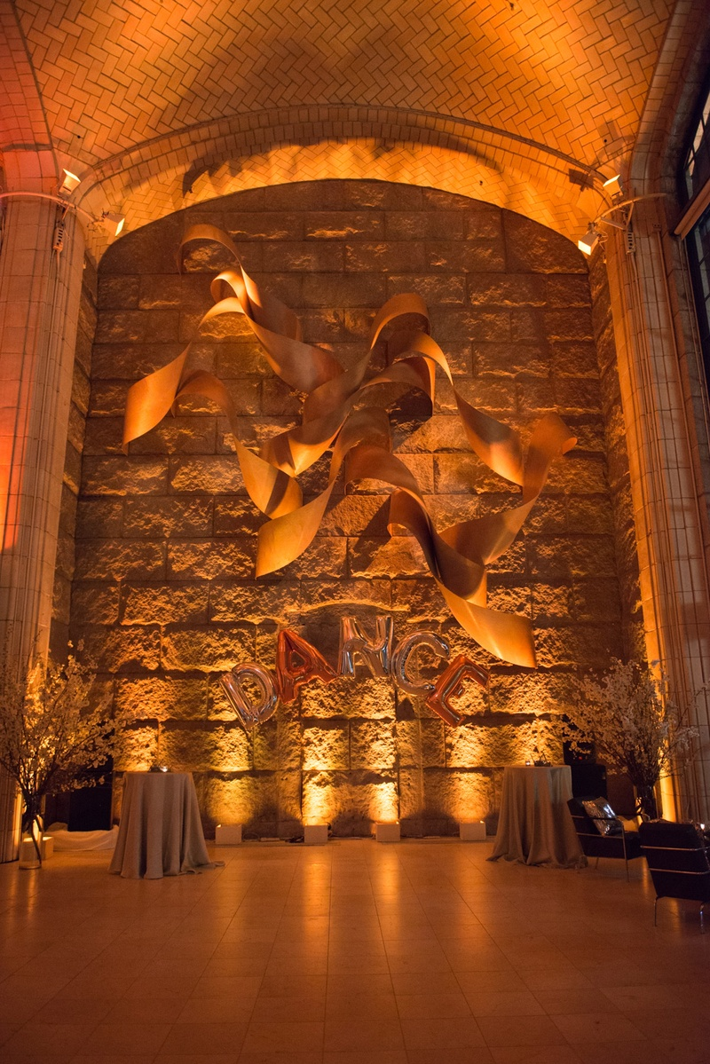 bright uplighting and tall ceilings in this couples new york city cocktail hour space with balloons