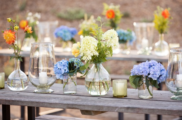 Picnic tables topped with flowers in glass vases of different sizes