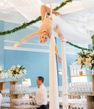 Wedding reception special silk aerial performer at reception over bar and server greenery garland