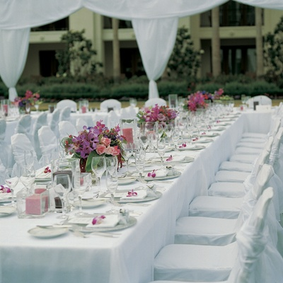 White tables and chairs with vibrant flowers