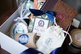 Welcome box with cookie featuring monogram, wedding weekend itinerary with magnolia print, book