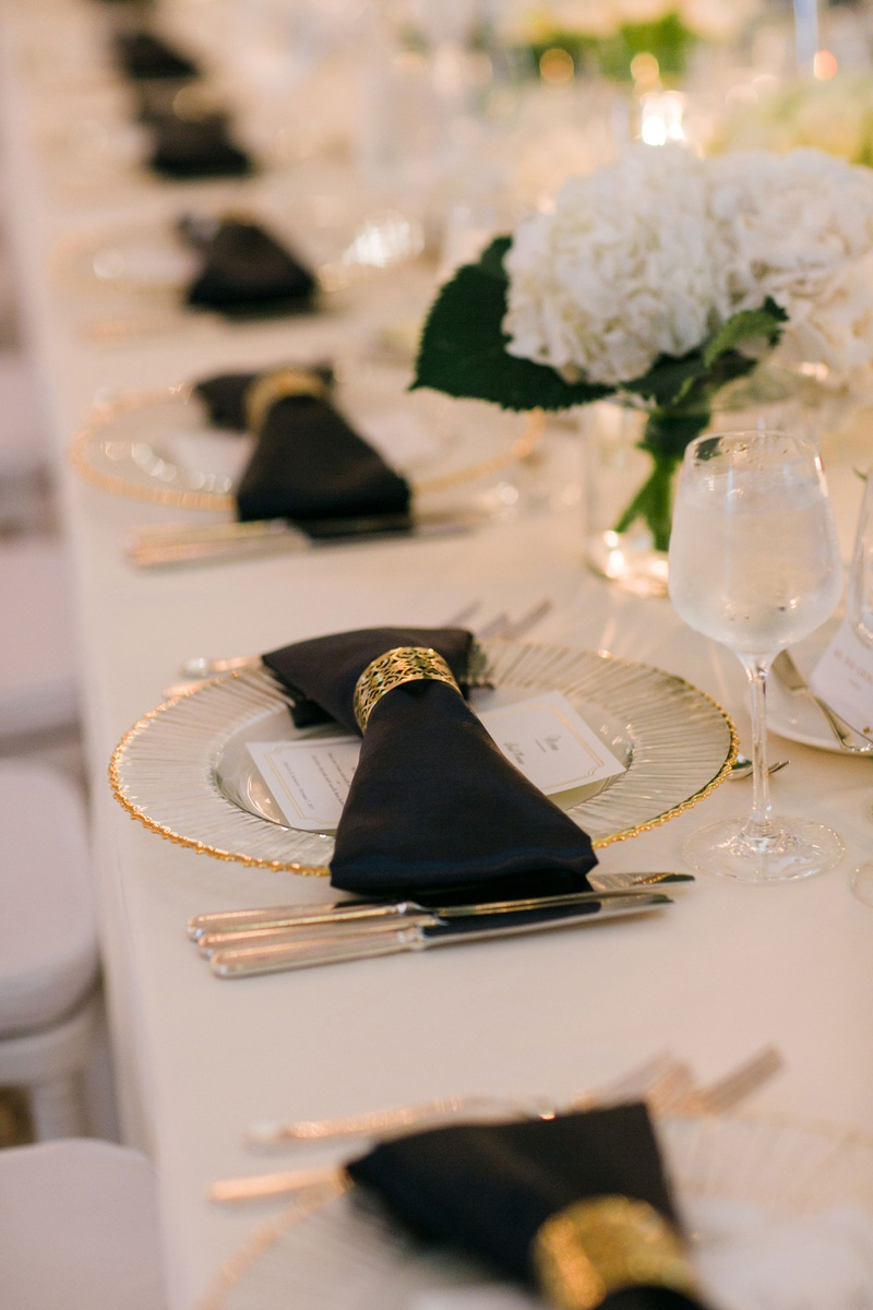 wedding reception long table white linen gold charger black napkin bow with gold napkin ring