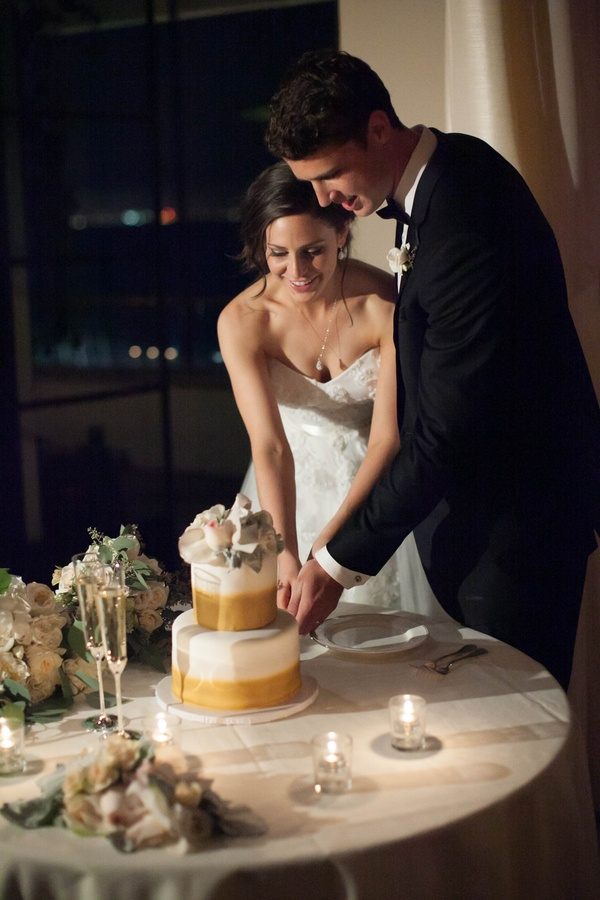 bride in strapless wedding dress and groom in tuxedo cut two-tiered white cake with gold airbrushing