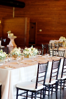Wedding reception with tables covered in white linens, black chairs, and white flowers