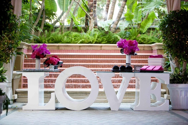 Large letter L-O-V-E table with hot pink flowers
