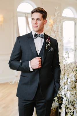 groom in black suit with black, grey, and white floral bow tie and matching pocket square
