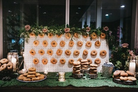 wedding dessert table with wall of apple cider donuts and plates of more donuts