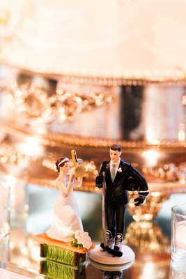 tiny statues of a bride cheerleader and groom hockey player