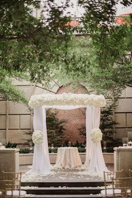 Wedding ceremony outside at hotel white chuppah and ivory flowers on top and on sides altar