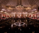 wedding reception ballroom black dance floor white monogram chandelier red rose centerpieces