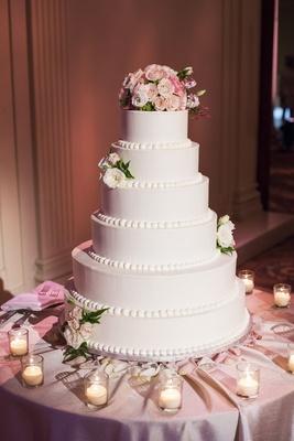 White wedding cake with beading and fresh roses