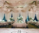 Ceiling drapery chandeliers white cream table linens green centerpieces dance floor decal