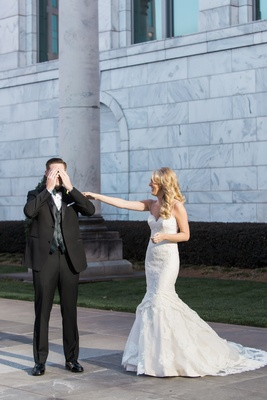 Groom in tuxedo and bow tie covers eyes as bride taps on his shoulder during first look