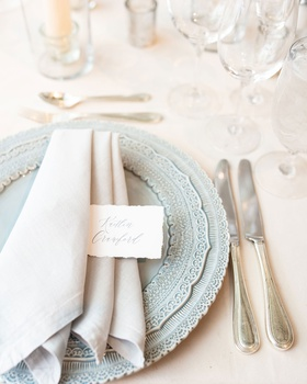 wedding reception place setting light blue charger plate light grey napkin torn place card