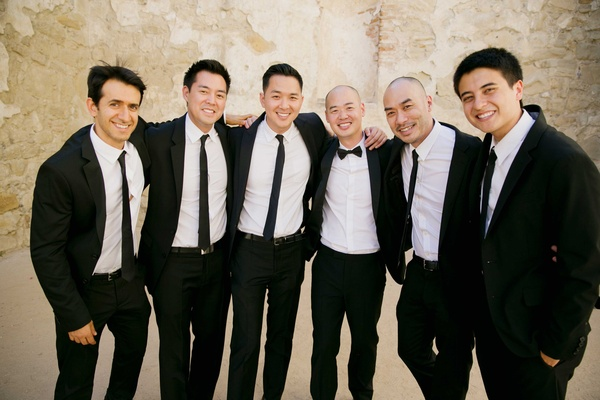 groom in black tuxedo and bow tie, groomsmen in tuxedos and black skinny ties