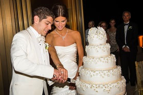 Bride in a Vera Wang gown and groom a white tuxedo coat cut white wedding cake with flowers