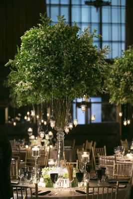 Wedding reception table with tall vase filled with foliage branches, suspended votive candles