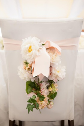 White and pink flowers hanging from pink ribbon on chair