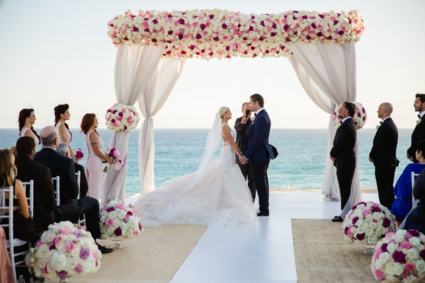 Bride in Galia Lahav wedding dress with groom in colored suit under pink white chuppah beach wedding