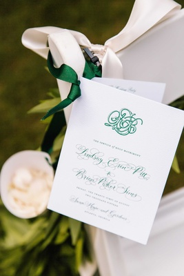 Wedding ceremony program green monogram and calligraphy on white chair with toss flower petals