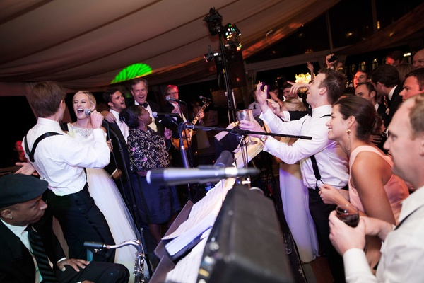 a fun loving bride and groom join their reception band onstage to sing a song
