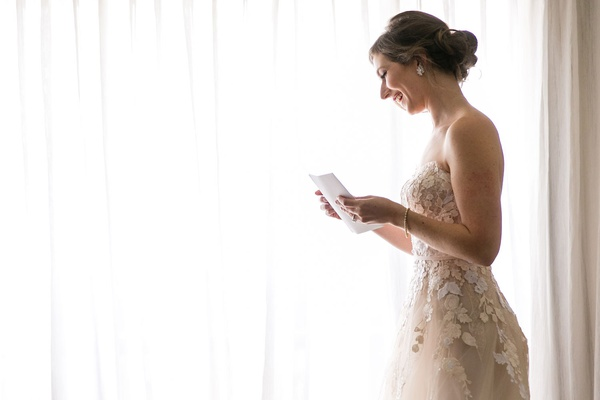 wedding bridal suite getting ready strapless wedding dress reading note from groom husband
