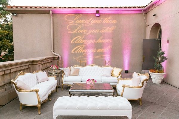 Vow renewal anniversary party lounge area with gold white furniture and projected sign on wall