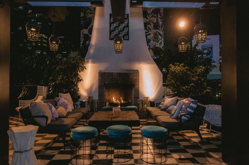wedding reception lounge area lanterns overhead checkerboard floor fireplace ottoman velvet