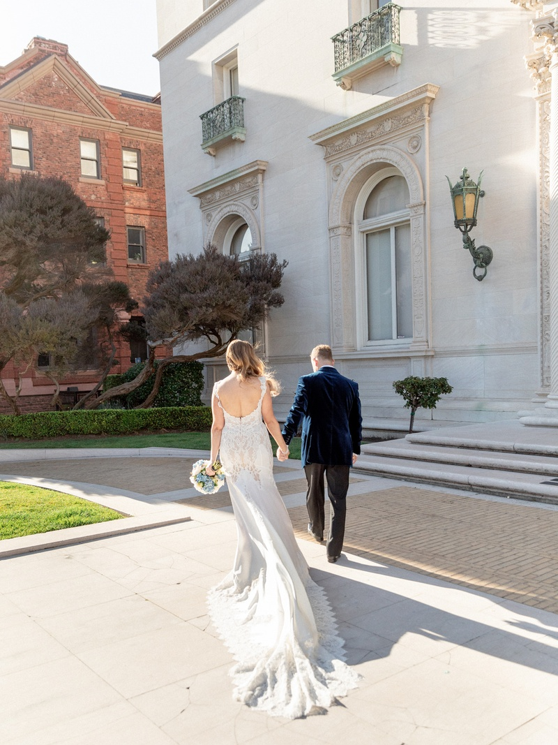 back view of bride in pnina tornai holding hands with groom in blue velvet jacket