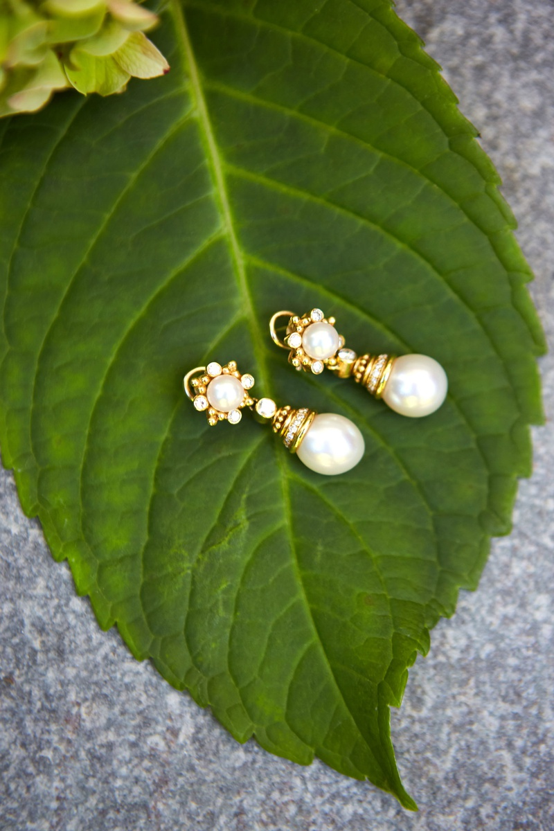 classic wedding jewelry yellow gold drop earrings with pearls and diamonds on green leaf detail shot