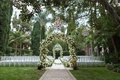 The Beverly Hills Hotel outdoor wedding ceremony with greenery and white flowers palm trees chairs