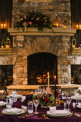 cozy rustic tablescape with purple table linens and low floral arrangements in front of fireplace