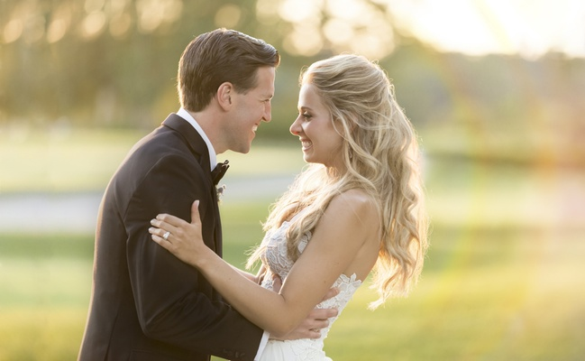 blonde bride with hair half up smiles with groom, groom grips bride on the waist