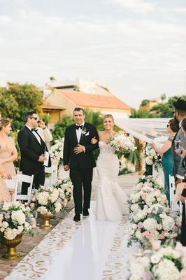 bride in mermaid wedding dress walking down white aisle gold scroll motif white pink flowers father
