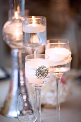 Floating candles in wedding centerpiece tall glass votives with ribbon and jewel decal