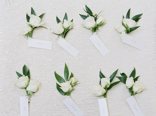 boutonnieres with two small roses and green leaves