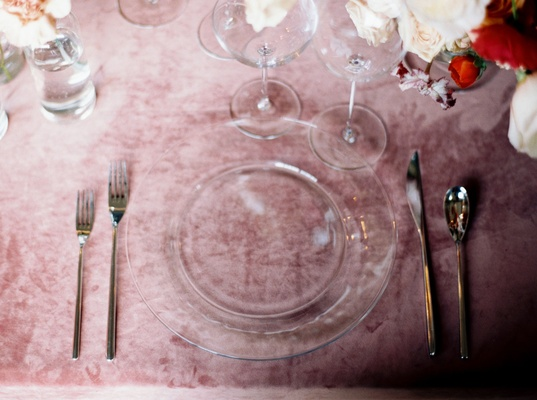 Place setting wedding reception clear charger plate and silver flatware pink velvet linens reception