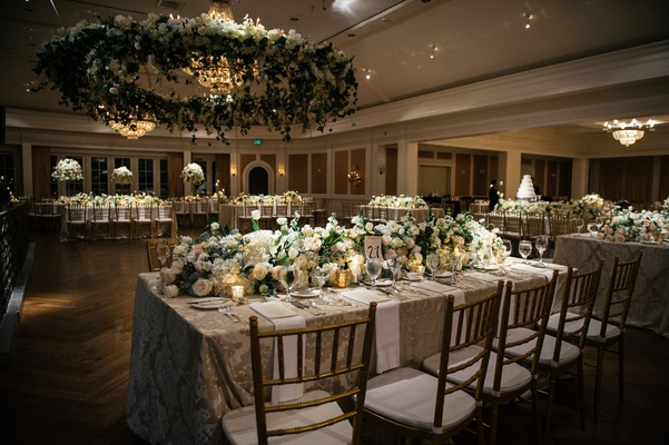 Wreath of flowers over dance floor linens beige gold chairs low centerpieces on rectangle tables