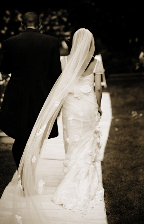 Sepia photo of bride in a Claire Pettibone lace gown and groom in black tails exit the ceremony