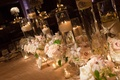 Reception table with floating candle and orchid rose flower arrangements