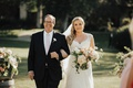 father of the bride in black suite and blush tie arm in arm with bride in lace cap-sleeve gown