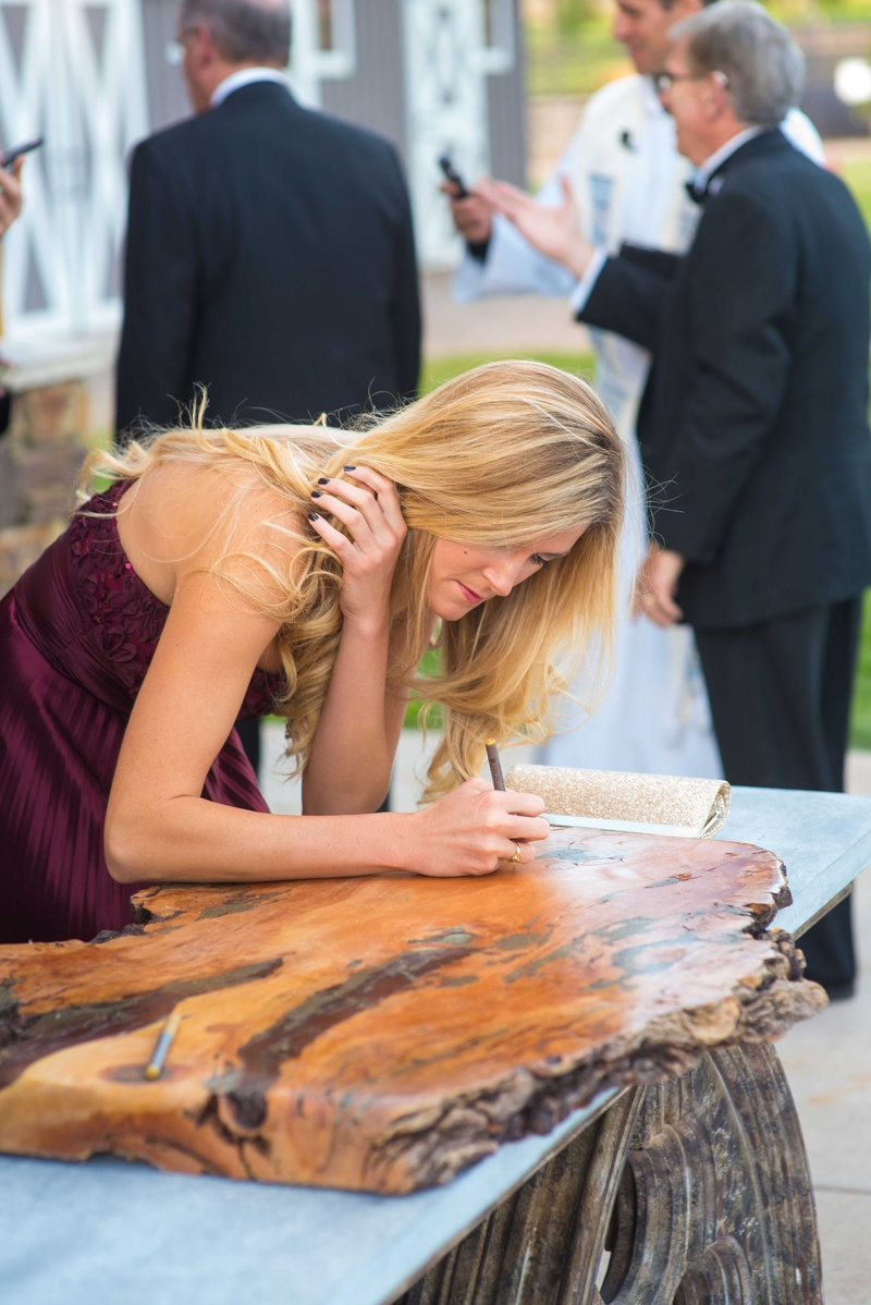 Guest in burgundy dress signing slab of polished wood before or after wedding ceremony