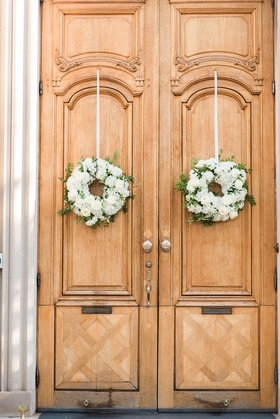 Wedding ceremony at the Meridian House white flower wreaths on tall wood doors greenery ribbon